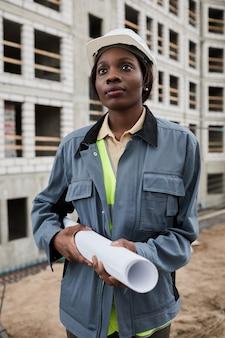 Verticaal portret van jonge vrouwelijke ingenieur die zich voordeed op de bouwplaats