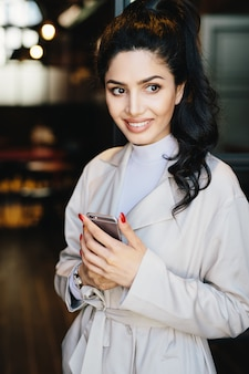 Verticaal portret van mooie donkerbruine vrouw in modieuze kleren die rode smartphone van de manicureholding hebben