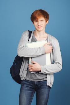 Verticaal portret van mooie jonge vrolijke mannelijke student in casual outfit met rugzak glimlachen, met veel notebooks in handen, met tevreden meningsuiting.