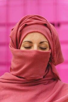 Verticaal portret van moslimvrouw die hiyab draagt met gesloten ogen. culturele diversiteit en religie.