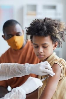 Verticaal portret van onherkenbare verpleegster die afro-amerikaanse jongen vaccineert tegen covid in kliniek of ziekenhuis