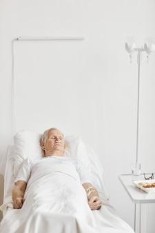 Verticaal portret van senior man liggend op bed in ziekenhuiskamer met iv infuus en zuurstofondersteuning, kopieer ruimte