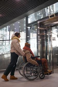 Verticaal portret van volledige lengte van een afro-amerikaanse man in een rolstoel die een toegankelijke lift gebruikt met een jonge vrouw die hem helpt in de stedelijke stad