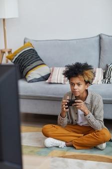 Verticaal portret van volledige lengte van gefocuste afro-amerikaanse jongen die thuis videogames speelt en gamepad vasthoudt terwijl hij op de vloer zit, kopieer ruimte