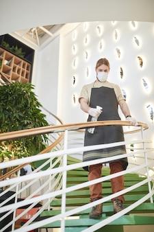 Verticaal portret van volledige lengte van mannelijke cafémedewerker die een masker draagt terwijl hij trapleuningen ontsmet in een milieuvriendelijk designinterieur