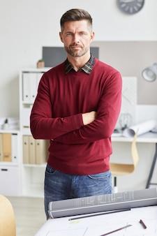 Verticaal portret van volwassen bebaarde architect permanent met gekruiste armen en terwijl poseren door tekenbureau op de werkplek