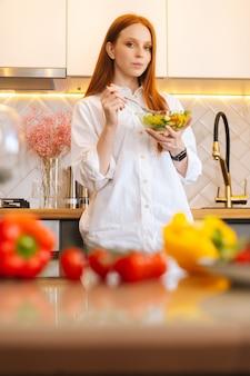Verticaal portret van vrij aantrekkelijke jonge roodharige vrouw die verse vegetarische salade eet die geniet van