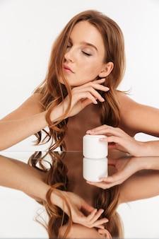Verticaal schoonheidsportret van gembervrouw met lang haar en gesloten oogzitting door de spiegeltafel met lichaamscrème
