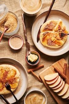 Verticaal schot van appelpannenkoekjes met koffieappelen en andere kookingrediënten op tafel