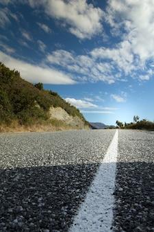 Verticaal schot van asfaltweg onder een bewolkte hemel