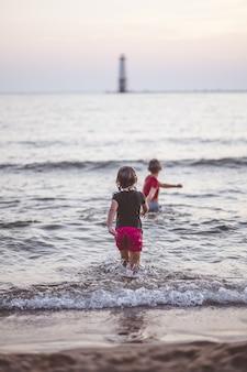 Verticaal schot van baby's die in een zee spelen