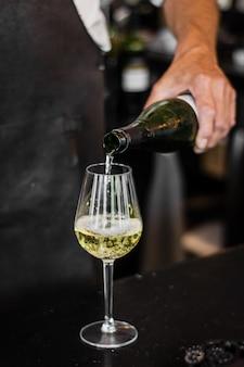 Verticaal schot van barman gietende wijn in een glas