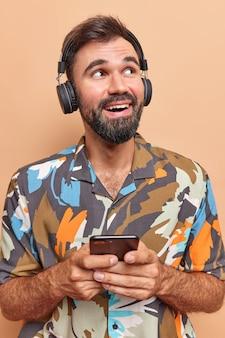 Verticaal schot van bebaarde vrolijke man houdt mobiele telefoon vast en luistert muziek via draadloze koptelefoon