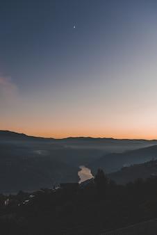 Verticaal schot van bergen en een meer onder een blauwe hemel