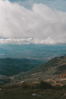 Verticaal schot van bergen onder een bewolkte hemel
