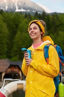 Verticaal schot van blij jonge europese vrouw in gele anorak met rugzak, vormt op vlot boot tegen rotsachtige bergen en bos