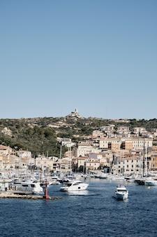 Verticaal schot van boten op het water dichtbij gebouwen op de heuvel met een blauwe hemel in
