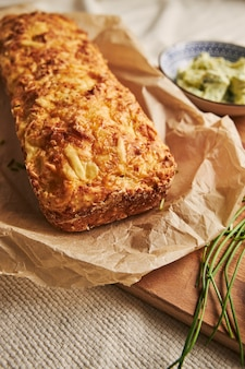 Verticaal schot van brood met kaas, kruidenboter op een hout