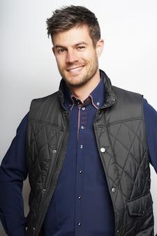 Verticaal schot van charmante man in een blauw klassiek shirt en zwart vest geïsoleerd op een witte achtergrond