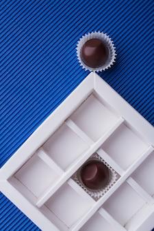 Verticaal schot van chocoladedoos met bruine snoepjes op blauwe achtergrond