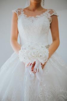 Verticaal schot van de bruid die een mooie witte huwelijkstoga op grijs draagt