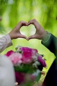 Verticaal schot van de bruid en de bruidegom die een hart met hun handen maken