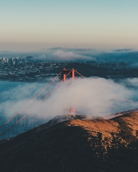 Verticaal schot van de golden gate bridge achter de wolken met gebouwen in de verte