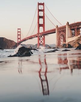 Verticaal schot van de golden gate bridge onder een bewolkte hemel