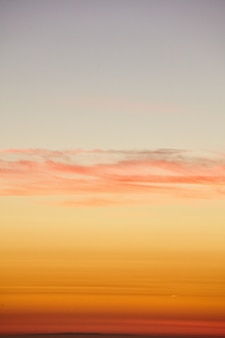 Verticaal schot van de gouden zonsonderganghemel over de stille oceaan