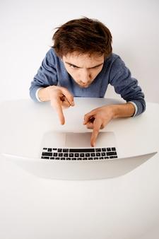 Verticaal schot van de jonge mens, verveelde de beambte moedigt aan om te werken, niet uit te stellen, wijzend op laptopscherm