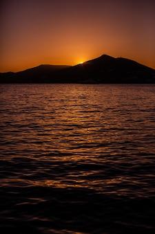 Verticaal schot van de ondergaande zon achter een berg in naxos, griekenland