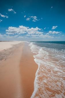Verticaal schot van de schuimende golven die aan het zandige strand onder de mooie blauwe hemel komen