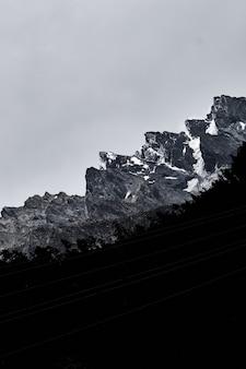 Verticaal schot van de silhouetten van bomen en kabellijnen onder de besneeuwde rotsen
