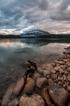 Verticaal schot van de stenen in het transparante meer onder de donkere bewolkte hemel
