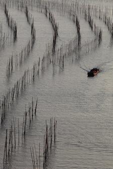 Verticaal schot van de vissersboot in de oceaan overdag in xia pu, china