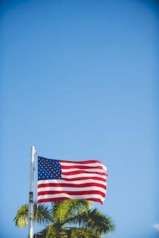 Verticaal schot van de vlag van verenigde staten op een pool met een blauwe hemel