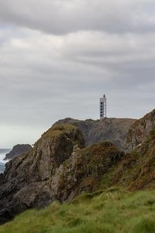 Verticaal schot van de vuurtoren van meares bovenop een berg op een bewolkte dag in galicië, spanje