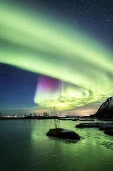 Verticaal schot van de weerspiegeling van het mooie noorderlicht in het water bij nacht in noorwegen