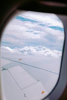 Verticaal schot van de wolken die uit een vliegtuigvenster worden gevangen
