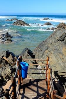 Verticaal schot van de zee met golven die de rotsen onder een blauwe hemel raken