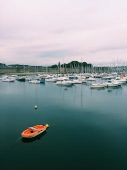 Verticaal schot van diverse boten op de watermassa onder een bewolkte hemel