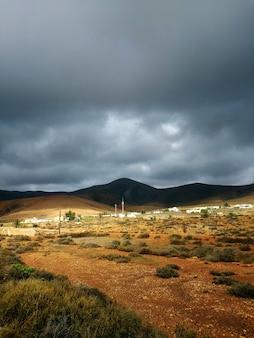 Verticaal schot van droge vallei en heuvels in schaduwen vóór het stormachtige weer in fuerteventura, spanje