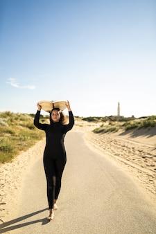 Verticaal schot van een aantrekkelijk wijfje dat een surfplank boven haar hoofd draagt