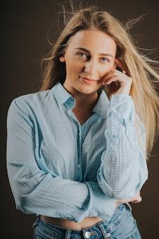 Verticaal schot van een aantrekkelijke blonde vrouw in spijkerbroek en een kort shirt poseren