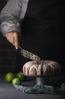 Verticaal schot van een banketbakker die een citroentaart met wit glazuur snijdt