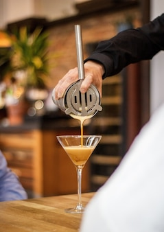 Verticaal schot van een barman die de cocktail in een glas met een vage achtergrond gieten