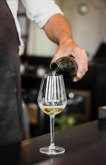 Verticaal schot van een barman die een wijn giet in een glas