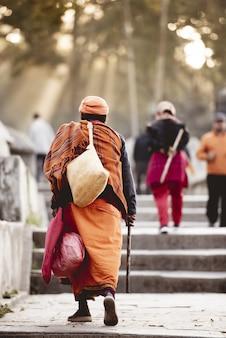 Verticaal schot van een bejaarde die hindoese gewaden met een vage achtergrond draagt