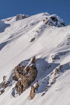 Verticaal schot van een bergachtig landschap dat in mooie witte sneeuw in sainte foy, franse alpen wordt behandeld