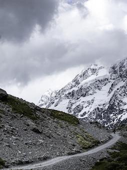 Verticaal schot van een bergpad op grijze wolken